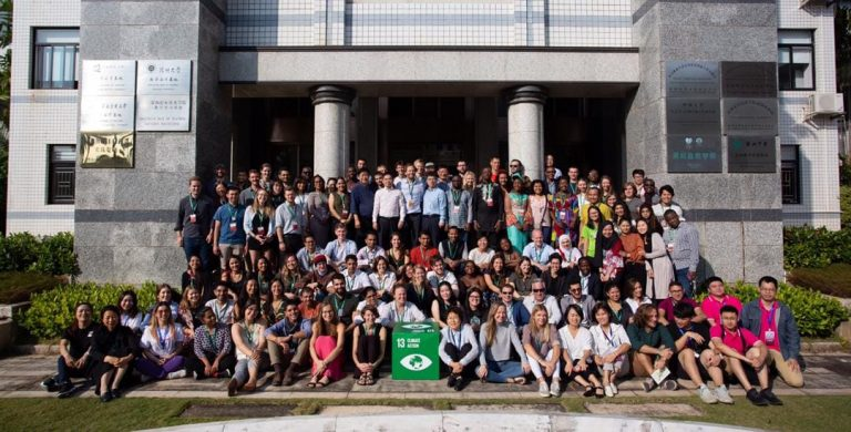 The UNLEASH UN-SDG Goal 13 - Climate Action Team (talents, facilitators, volunteers and gardens staff) gather in front of a building in Fairy Lake Botanic Garden (over 50 people) holding a green Climate Action block in the center