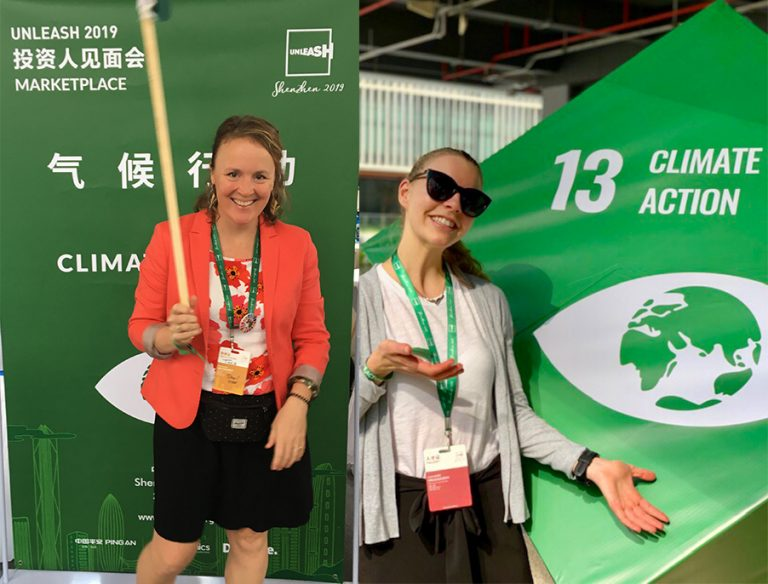 Tara Moreau waving the Climate Action flag in front of green SDG Climate Action poster; Andrea Byfigulien poses in front of big green SDG cube for SDG 13 - Climate Action