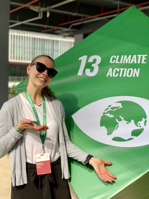 Andrea poses in front of the SDG 13: Climate Action cube