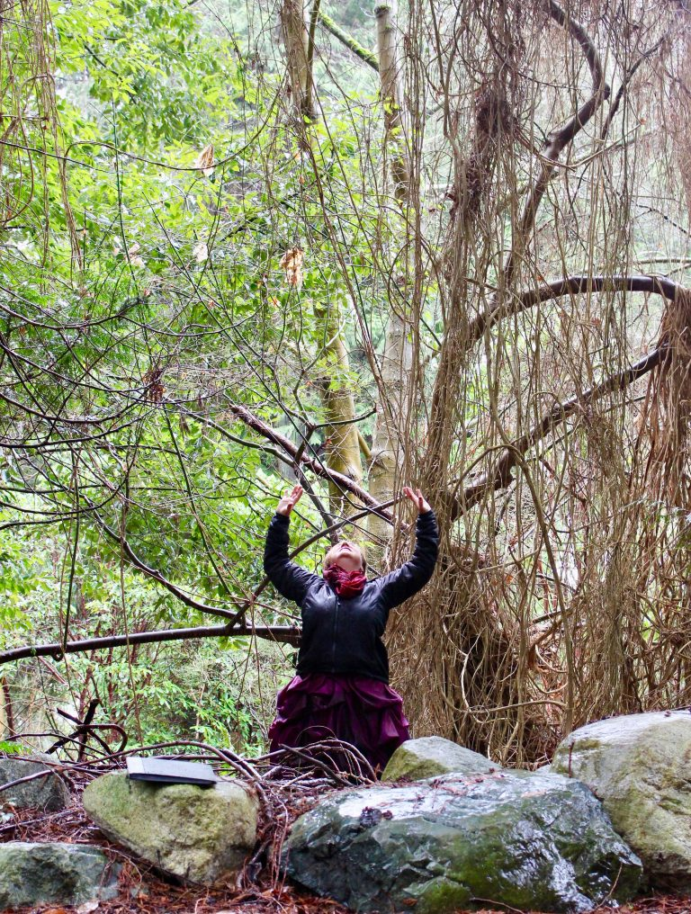 Celeste Snowber raises her arms to the skies; trees in background