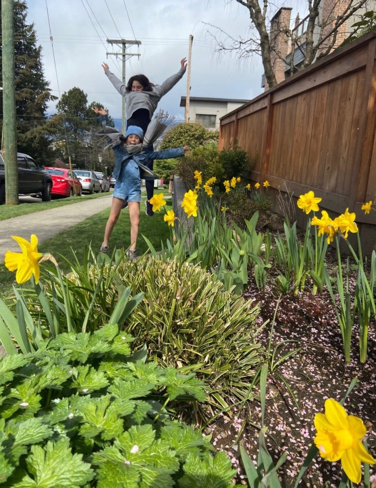 Two kids in the background, daffodil bed in the foreground of sidewalk