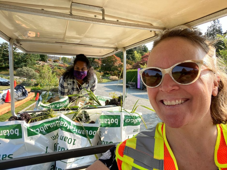 Tara Moreau and Akhila Varghese with bags of produce in golf cart