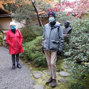 FOGs pose for photo by bushes and statue in Nitobe Memorial Garden in fall