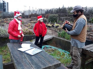 FOGs in festive outfits in the Garden consulting a horticulturist